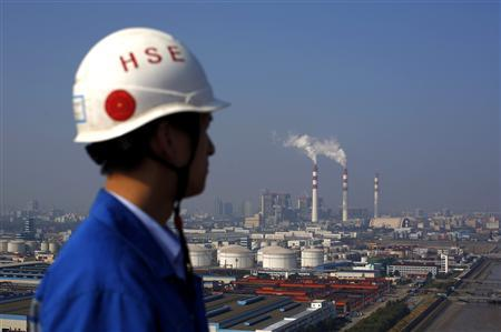 Smoke rises from the chimneys of a thermal power plant as a worker stands on a crane at a shipyard in Shanghai, November 5, 2013. China will be ''flexible'' in U.N. talks for a new global climate change deal, but the key to progress is getting rich nations to keep pledges to fund mitigation steps by poorer countries, the country's top climate change official said on Tuesday. REUTERS/Carlos Barria