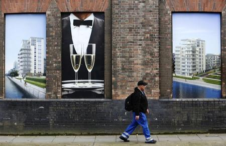 A man passes advertising for new flats under construction in west London October 25, 2013. REUTERS/Luke MacGregor