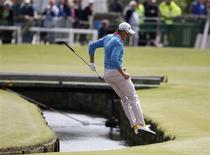 Sweden's Henrik Stenson jumps over the Swilcan Burn after chipping onto the first green during the final round of the British Open golf championship on the Old Course in St. Andrews, Scotland, July 18, 2010. REUTERS/Phil Noble