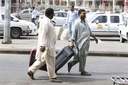 Foreign workers pull their luggage along a street in Riyadh November 4, 2013. REUTERS/Faisal Al Nasser