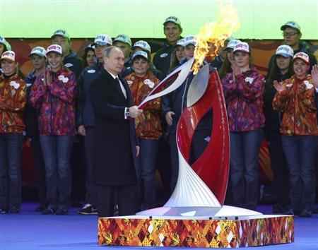Russian President Vladimir Putin holds a lighted Olympic torch during a ceremony to mark the start of the Sochi 2014 Winter Olympic torch relay in Moscow October 6, 2013. REUTERS/Sergei Karpukhin