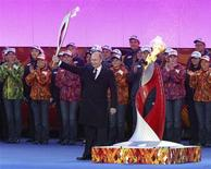 Russian President Vladimir Putin holds a lighted Olympic torch during a ceremony to mark the start of the Sochi 2014 Winter Olympics torch relay in Moscow October 6, 2013. REUTERS/Sergei Karpukhin