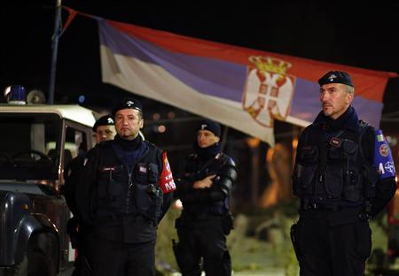 Italian Carabinieri, who are members of the NATO Kosovo Force (KFOR), stand in front of a Serbian national flag as they secure the main bridge in the northern part of the ethnically-divided town of Mitrovica, November 3, 2013. REUTERS/Marko Djurica