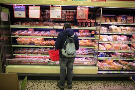 Jose Manuel Abel, 47, shops for food at a supermarket after finishing work in Munich October 10, 2013. REUTERS/Marcelo del Pozo/Files
