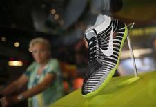 Una mujer observa una zapatilla de Nike en una tienda en Santa Monica, EEUU, sep 25 2013. La actividad de negocios en el amplio sector de servicios de Estados Unidos se aceleró en octubre y las empresas contrataron a trabajadores pese a la paralización parcial del Gobierno, aunque el segmento de nuevos pedidos disminuyó por segundo mes consecutivo, mostró el martes un informe de la industria. REUTERS/Lucy Nicholson