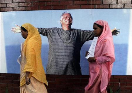 Employees of Grameen Bank walk in front of a portrait of Nobel laurate Muhammad Yunus in Dhaka March 8, 2011. REUTERS/Andrew Biraj/Files