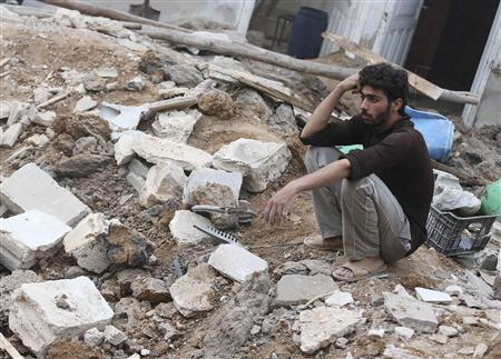 A man sits on the rubble of the damaged buildings by what activists said was an air strike by forces loyal to Syrian President Bashar al-Assad in the Duma neighbourhood of Damascus November 4, 2013. REUTERS/Bassam Khabieh