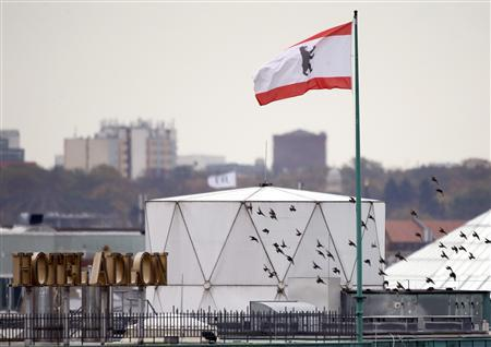 Birds fly beside a white covered structure and a Berlin city flag next to the roof of the British embassy in Berlin, November 5, 2013. REUTERS/Fabrizio Bensch