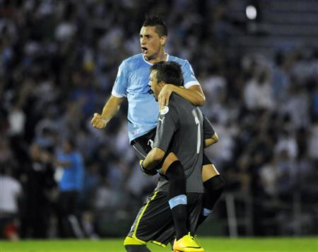Uruguay's goalkeeper Fernando Muslera celebrates with teammate Jose Gimenez after their team scored against Colombia during their 2014 World Cup qualifying soccer match in Montevideo, September 10, 2013. REUTERS/Martin Cerchiari