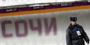 """Сотрудник российской полиции у олимпийской трассы на горнолыжном курорте """"Роза Хутор"""" близ Сочи 22 февраля 2013 года. Российская полиция задержала и одолела вопросами двух норвежских журналистов, отправившихся за репортажем в предолимпийский Сочи, сообщили правозащитная организация и телевидение Норвегии. REUTERS/Kai Pfaffenbach"""