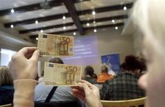 People learn to differentiate between original (top) and counterfeit euro banknotes during a workshop in Salacgriva September 24, 2013. REUTERS/Ints Kalnins