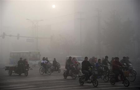 Residents ride bicycles along a street amid heavy haze in Xingtai, Hebei province November 3, 2013. Dense smog has periodically shrouded major cities in north and northeast China in recent years, raising increasing public discontent, Xinhua News Agency reported. REUTERS/China Daily