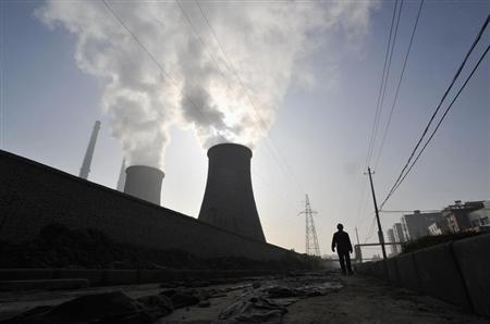 A man walks past a coal-burning power plant in Xiangfan, Hubei province November 19, 2010. REUTERS/Stringer