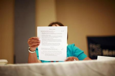 A woman looks over a resume during a job fair in New York June 11, 2012. REUTERS/Eric Thayer