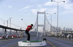 U.S. golfer Tiger Woods hits a shot during an event to promote the upcoming Turkish Airlines Open golf tournament, on the Bosphorus Bridge that links the city's European and Asian sides, in Istanbul November 5, 2013. REUTERS/Murad Sezer