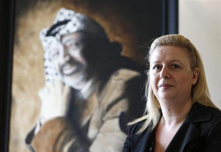 Suha Arafat poses near a portrait of her late husband and Palestinian leader Yasser Arafat before watching the wreath laying ceremony after her husband's exhumation in the West Bank city of Ramallah, on television from her apartment in Sliema, outside Valletta, November 27, 2012. REUTERS/Darrin Zammit Lupi