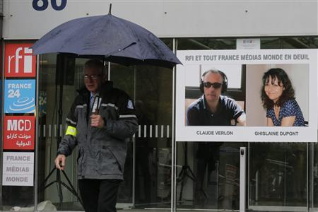 A poster with the portraits of reporter Ghislaine Dupont (R), 51, and radio technician Claude Verlon, 58, two French journalists killed in Mali last week, is seen at the entrance of Radio France Internationale building in Issy-les-Moulineaux near Paris November 5, 2013. REUTERS/Jacky Naegelen