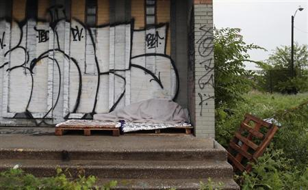 A homeless person sleeps under a blanket on the porch of a shuttered public school covered with graffiti in a once vibrant southwest neighborhood in Detroit, Michigan July 23, 2013. REUTERS/Rebecca Cook