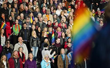 People sing the Russian national anthem while raising rainbow flags in solidarity with the lesbian, gay, bisexual and transgender (LGBT) community of Russia, as part of a film project called ''Live and Let Love'', at the Stockholm Olympic Stadium October 6, 2013. REUTERS/Erik Martensson/TT News Agency