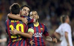 Barcelona's Lionel Messi (L) is congratulated by team mates Xavi (C) and Dani Alves after scoring his second goal against AC Milan during their Champions League soccer match at Nou Camp stadium in Barcelona November 6, 2013. REUTERS/Gustau Nacarino