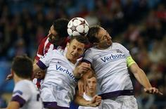 Atletico Madrid's Raul Garcia (L) fights to head the ball with Austria Vienna's Florian Mader (C) and Manuel Ortlechner during their Champions League Group G soccer match at Vicente Calderon stadium in Madrid November 6, 2013. REUTERS/Susana Vera