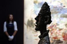 "A Sotheby's employee stands behind Alberto Giacometti's artwork ""Grande tete de Diego"" at Sotheby's auction house in London October 11, 2013. REUTERS/Stefan Wermuth"