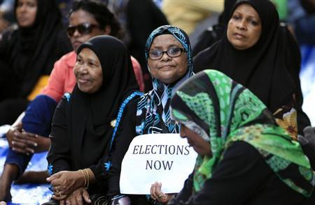 Supporters of presidential candidate Mohamed Nasheed, who was ousted as president in 2012 , sit as they block a road during a protest in Male October 19, 2013. REUTERS/Dinuka Liyanawatte