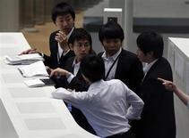 Сотрудники Токийской фондовой биржи 13 июня 2013 года. Азиатские фондовые рынки снизились в четверг в ожидании макроэкономической статистики США. REUTERS/Toru Hanai