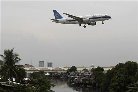 A China Southern Airlines aircraft flies over a slum before landing at Manila's International airport May 16, 2012. REUTERS/Romeo Ranoco/Files