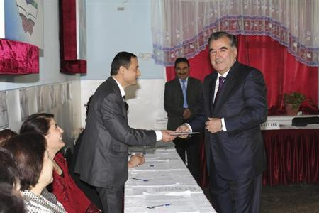 Tajikistan's President Imomali Rakhmon (R) receives his ballot from an electoral official during the presidential election in Dushanbe, in this November 6, 2013 handout photograph provided by Press Service of presidential administration of Tajikistan. REUTERS/Press Service of presidential administration of Tajikistan/Handout via Reuters
