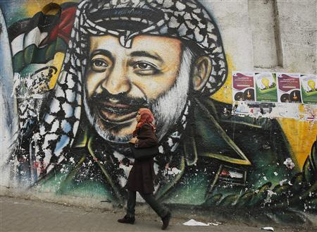 A Palestinian student walks past a mural depicting late Palestinian leader Yasser Arafat in Gaza City November 7, 2013. REUTERS/Suhaib Salem