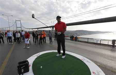 U.S. golfer Tiger Woods gets ready to hit a shot during an event to promote the upcoming Turkish Airlines Open golf tournament, on the Bosphorus Bridge that links the city's European and Asian sides, in Istanbul November 5, 2013. REUTERS/Murad Sezer