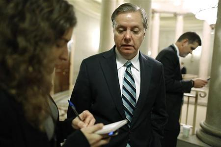 U.S. Senator Lindsey Graham (C) talks to a reporter as he arrives for a Republican Senate caucus meeting at the U.S. Capitol in Washington, October 16, 2013. REUTERS/Jonathan Ernst