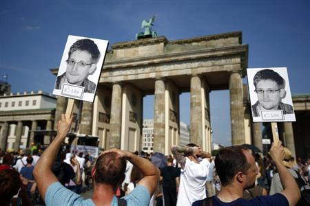 Protesters carry portraits of Edward Snowden during a demonstration against secret monitoring programmes PRISM, TEMPORA, INDECT and showing solidarity with whistleblowers Edward Snowden, Bradley Manning and others in front of Berlin's Brandenburg gate July 27, 2013. REUTERS/Pawel Kopczynski