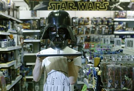 Employee Simon Domoney poses with a scale replica of Star Wars character Darth Vader's helmet at the Forbidden Planet memorabilia and comic store in London May 11, 2013. REUTERS/Luke MacGregor