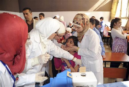 Syrian health workers administer polio vaccination to a girl at a school in Damascus, in this file photo taken by Syria's national news agency SANA on October 20, 2013. REUTERS/SANA/Handout via Reuters