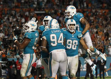 Miami Gardens, FL, USA; Miami Dolphins defensive end Cameron Wake (91) celebrates with defensive tackle Randy Starks (94) defensive tackle Jared Odrick (98) and safety Jimmy Wilson (27) after Wake's sack for a safety in overtime on Cincinnati Bengals quarterback Andy Dalton (not pictured) at Sun Life Stadium. Miami won 22-20. Mandatory Credit: Robert Mayer-USA TODAY Sports