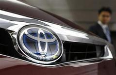 Посетитель изучает автомобиль Toyota в демонстрационном зале компании в Токио 8 мая 2013 года. Toyota Motor Corp сообщила, что отзывает 33.000 легковых машин, пикапов и коммерческих автомобилей для замены дефектной запчасти, которая может привести к отказу двигателя. REUTERS/Yuya Shino
