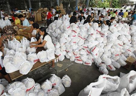 Volunteers pack relief goods inside a Department of Social Welfare and Development warehouse before shipping out to devastated provinces hit by Typhoon Haiyan in Manila November 8, 2013. REUTERS/Romeo Ranoco