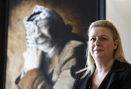 Suha Arafat poses near a portrait of her late husband and Palestinian leader Yasser Arafat before watching the wreath laying ceremony after her husband's exhumation in the West Bank city of Ramallah, on television from her apartment in Sliema, outside Valletta, November 27, 2012. REUTERS/Darrin Zammit Lupi/Files