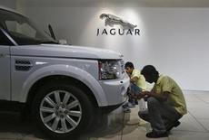 Showroom attendants polish a vehicle under a Jaguar logo at a Jaguar Land Rover showroom in Mumbai February 13, 2013. REUTERS/Vivek Prakash