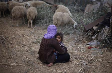 A Palestinian girl holds her sister as they sit outside their dwelling in al-Mugraga in the central Gaza Strip November 7, 2013. REUTERS/Ibraheem Abu Mustafa