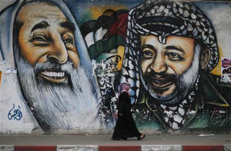 A Palestinian student walks past a mural depicting late Palestinian leader Yasser Arafat (R) and late Hamas spiritual leader Ahmed Yassin, in Gaza City November 7, 2013. REUTERS/Suhaib Salem