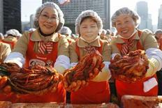 """Женщины держат кимчи во время благотворительной акции в Сеуле 15 ноября 2012 года. Если знаменитый """"индекс Биг-Мака"""" от журнала Economist вам кажется немного жирным, стоит обратить внимание на его более здоровую альтернативу - """"индекс кимчи"""", популярной по всему миру жгучей капусты, предлагаемый Южной Кореей. REUTERS/Kim Hong-Ji"""