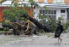 Homem caminha ao lado de árvore arrancada do chão por rajadas de vento trazidas pelo tufão Haiyan, na ilha Cebu, região central das Filipinas. O mais poderoso tufão do mundo neste ano e possivelmente o mais forte a atingir a terra na história castigou as Filipinas nesta sexta-feira, forçando mais de um milhão de pessoas a fugir, cortando o fornecimento de energia e destruindo casas. 8/11/2013. REUTERS/Zander Casas