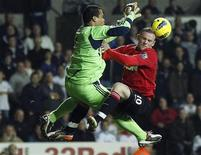Swansea City's Michel Vorm (L) challenges Manchester United's Wayne Rooney (R) during their English Premier League soccer match at the Liberty Stadium in Swansea, south Wales, November 19, 2011. REUTERS/Phil Noble