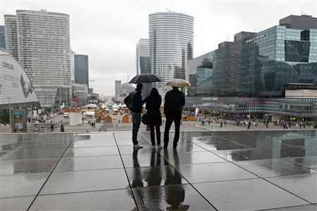 People are silhouetted as they shelter from rain under the Arche de la Defense, in the financial district west of Paris, November 8, 20123. Standard & Poor's lowered its long-term foreign and local currency sovereign credit ratings on the Republic of France on Friday by one notch to 'AA' from 'AA+'. REUTERS/Charles Platiau