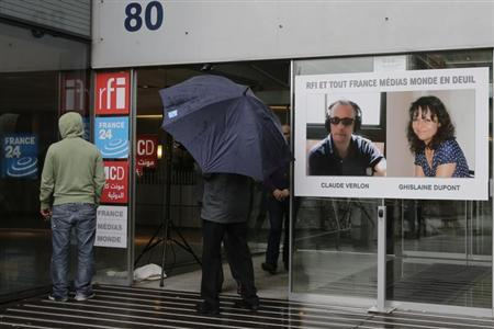 A poster with the portraits of reporter Ghislaine Dupont (R), 51, and radio technician Claude Verlon, 58, two French journalists killed in Mali last week is seen at the entrance of Radio France Internationale building in Issy-les-Moulineaux near Paris November 5, 2013. REUTERS/Jacky Naegelen