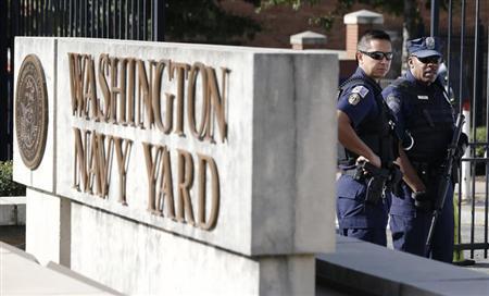 A Washington, DC Metropolitan police officer (L) and a Naval District Washington policemen (R) stand guard at the main gate of the Washington Navy Yard in Washington, September 17, 2013. REUTERS/Jason Reed