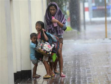 A mother takes refuge with her children as Typhoon Haiyan hits Cebu city, central Philippines November 8, 2013. REUTERS/Zander Casas